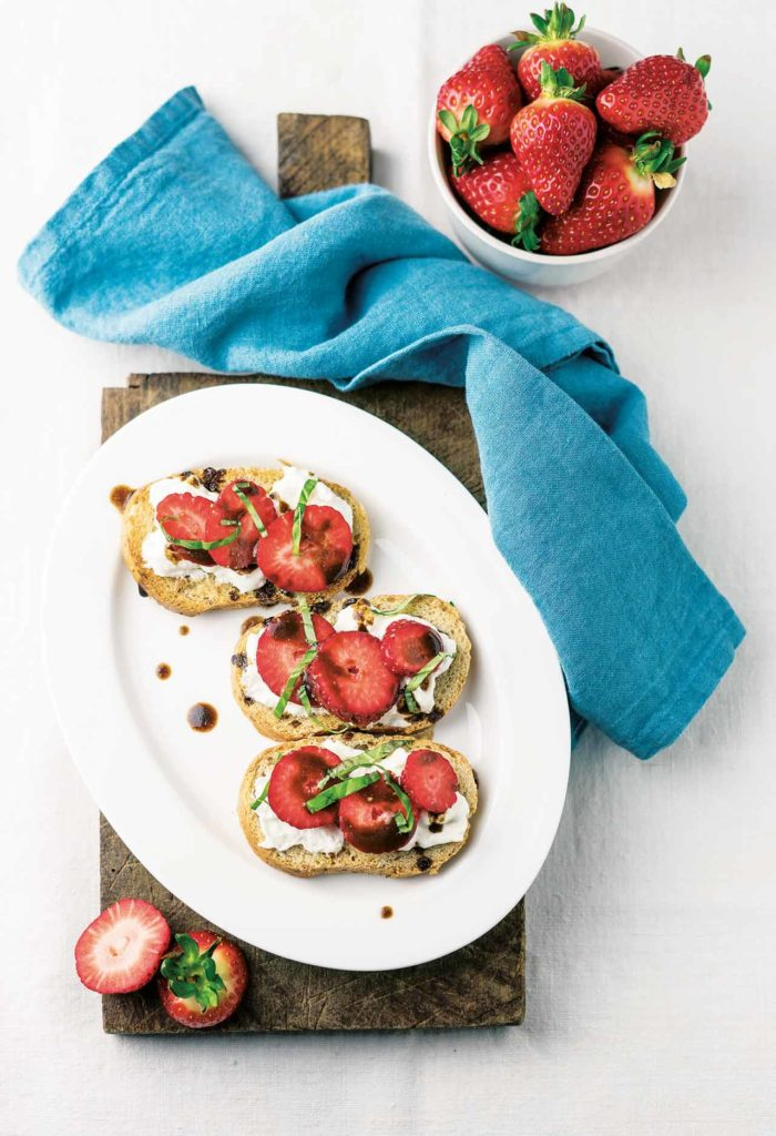 Crostoni (toasted slices of bread) with strawberries and stracciatella cheese